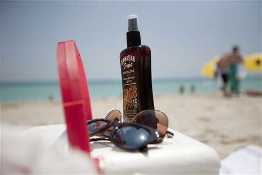 This Wednesday, May 9, 2012 photo shows a bottle of sun tan lotion and sunglasses on top of a cooler carried onto Miami Beach, Fla. by tourists. In a study released Thursday, May 10, 2012, the Centers for Disease Control and Prevention says half of adults under 30 say they've had a sunburn at least once in the past year. Experts worry it's a sign young people aren't paying much attention to warnings about skin cancer, including the deadliest kind. (AP Photo/J Pat Carter) Photo: AP / AP