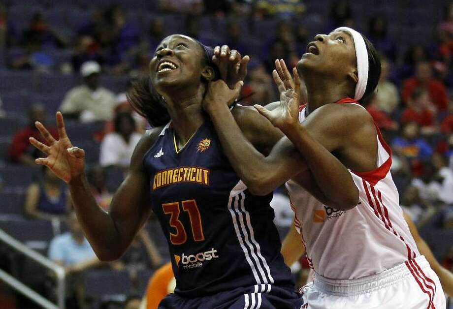ASSOCIATED PRESS Connecticut Sun center Tina Charles (31) gets tangled up with Washington Mystics center Michelle Snow (2) during the second half of a WNBA game Tuesday in Washington. The Sun won 77-70.