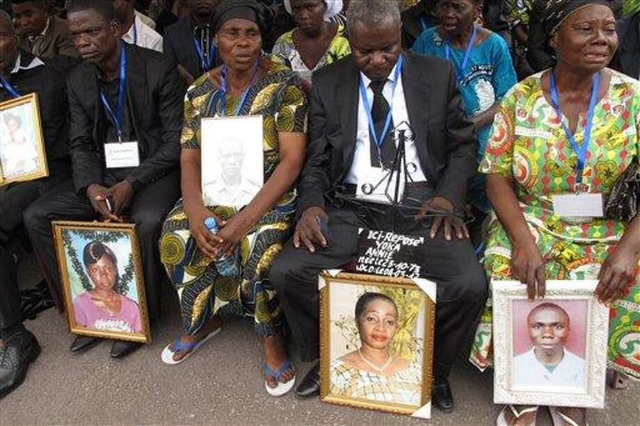 Families hold the portraits of their dead relatives during a mass funeral in Brazzaville, Republic of Congo Sunday for some of the victims of the catastrophic explosion March 4, which left at least 246 dead. A fire inside the main military arms depot caused a series of blast so strong that houses were flattened, crushing scores of people. Only 159 of the bodies could be identified in time for the mass funeral. Associated Press Photo: AP / AP