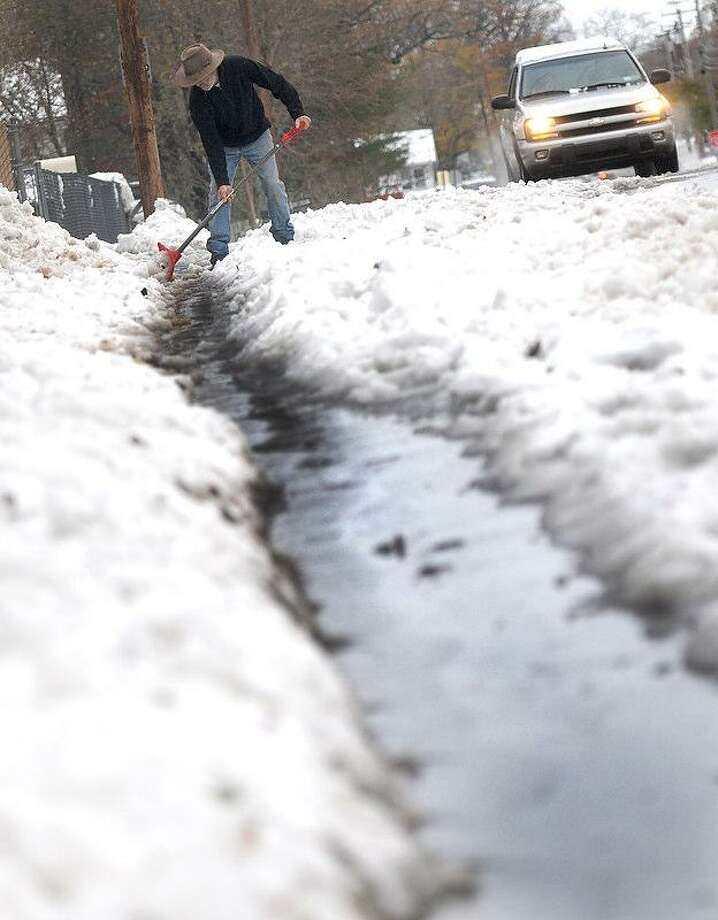 Martin Petry of East Haven shovels a drainage ditch Thursday for the melting snow on a sidewalk in his neighborhood on Coe Avenue and Cold Spring Street in East Haven. Peter Hvizdak / New Haven Register Photo: New Haven Register / ©Peter Hvizdak /  New Haven Register