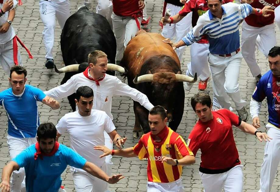 Revelers run on the Callejon way surrounding by two Cebada Gago ranch fighting bull, during the third running of the bulls at the San Fermin fiestas, in Pamplona northern Spain, Monday, July 9, 2012. (AP Photo/Alvaro Barrientos) Photo: AP / AP2012