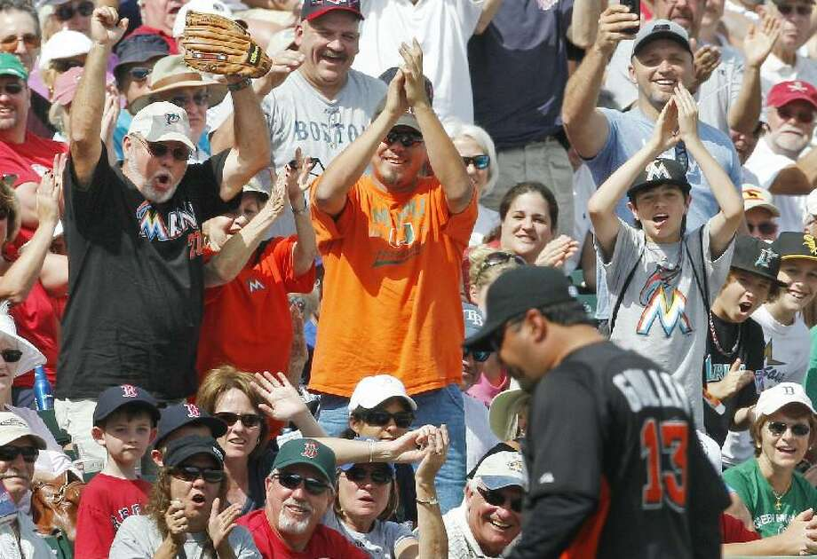 ASSOCIATED PRESS Miami Marlins fans cheer as manager Ozzie Guillen, right, walks off the field after being ejected for arguing a call in the sixth inning of a spring training game against the Boston Red Sox Monday in Fort Myers, Fla