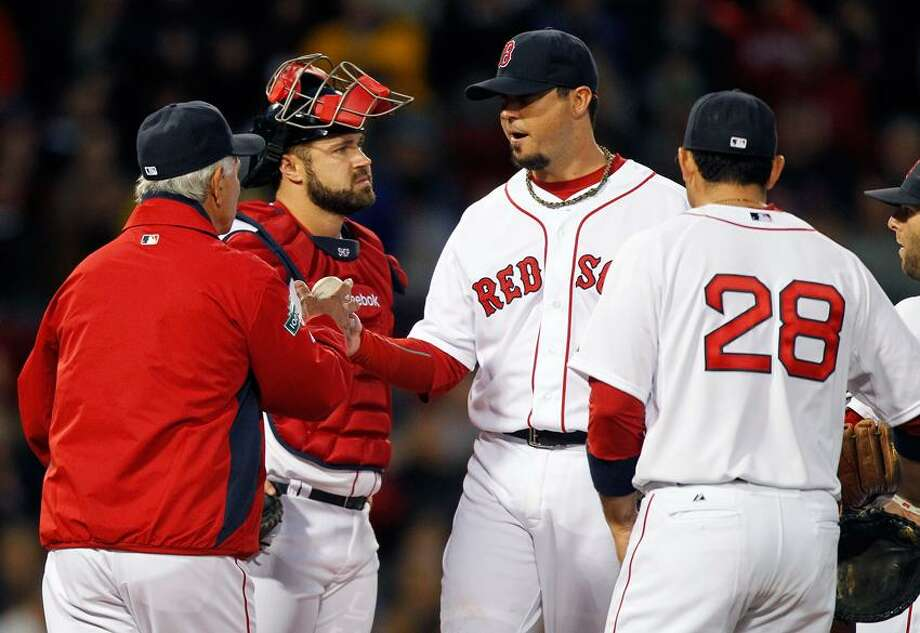 Boston Red Sox pitcher Josh Beckett, second from right, hands the ball to manager Bobby Valentine, left, and leaves the game as catcher Kelly Shoppach, second from left, and Adrian Gonzalez (28) watch in the third inning of a baseball game against the Cleveland Indians in Boston, Thursday, May 10, 2012. (AP Photo/Michael Dwyer Photo: AP / AP
