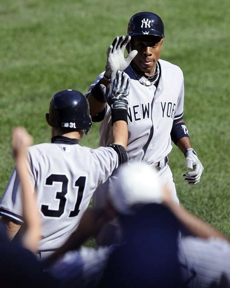 New York Yankees' Curtis Granderson, right, celebrates his home run with teammate Ichiro Suzuki (31), of Japan, during the sixth inning of a baseball game against the Baltimore Orioles, Sunday, Sept. 9, 2012, in Baltimore. The Yankees won 13-3. (AP Photo/Nick Wass) Photo: AP / AP2012