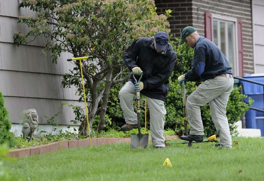 Law enforcement agents dig in the front yard of the home of reputed Connecticut mobster Robert Gentile in Manchester, Thursday.  Gentile's lawyer A. Ryan McGuigan says the FBI warrant allows the use of ground-penetrating radar and believes they are looking for paintings stolen from Boston's Isabella Stewart Gardener Museum in 1990, worth half a billion dollars. Photo: AP / AP2012