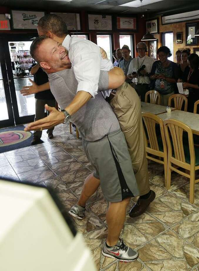 President Barack Obama, right, is picked-up and lifted off the ground by Scott Van Duzer, left, owner of Big Apple Pizza and Pasta Italian Restaurant, during an unannounced stop, Sunday, Sept. 9, 2012, in Ft. Pierce, Fla. (AP Photo/Pablo Martinez Monsivais) Photo: AP / AP2012