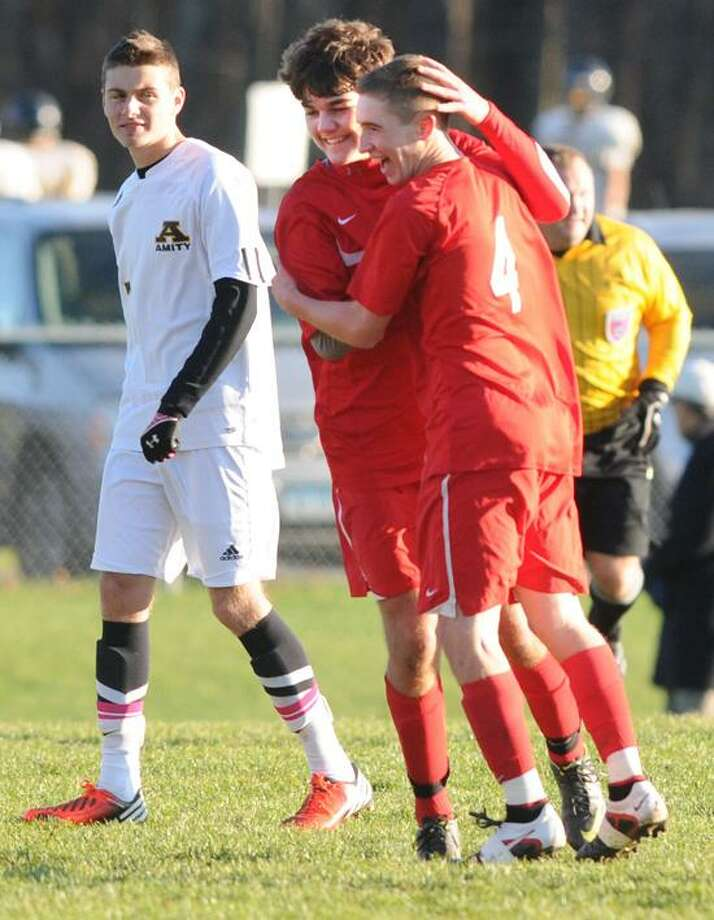 Branford's Julian Pino, left, congratulates teammate Hunter Duval after Duval's goal against Amity Monday. Branford is the No. 9 seed in the Class L state tournament. Mara Lavitt/New Haven Register  11/5/12