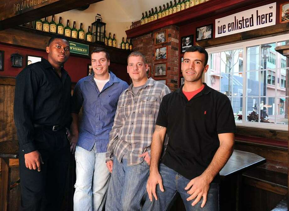 Former soldiers who enlisted at the recruiting center at 157 Orange St., which is now O'Tooles Pub. The pub reserves a special section of honor for the many who enlisted there. From left to right, Winston Daley of Bridgeport, Bryan Townsend of Watertown, Joseph Manio of Ansonia and Derek Torrellas of Clinton. Photo by Peter Casolino/New Haven Register