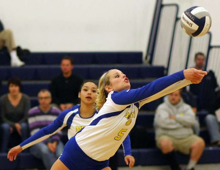 "Special to the Press  11.06.12  Mercy's Nicole Kana reaches for a block in Tuesday night's volleyball gave against Amity.  Amity won, 3-1. To buy a glossy print of this photo and more, visit <a href=""http://www.middletownpress.com"">www.middletownpress.com</a>. / a"