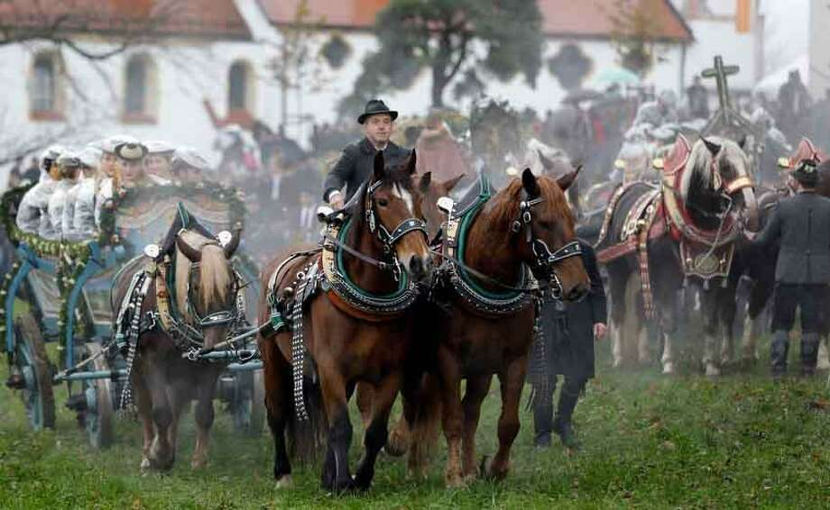 Horsemen steer their carriages over a rain-sodden meadow during the traditional Leonhardi pilgrimage in Bad Toelz, southern Germany, Tuesday, Nov. 6, 2012. The annual pilgrimage honors St. Leonhard, patron saint of the highland farmers for horses and livestock. (AP Photo/Matthias Schrader) Photo: ASSOCIATED PRESS / AP2012