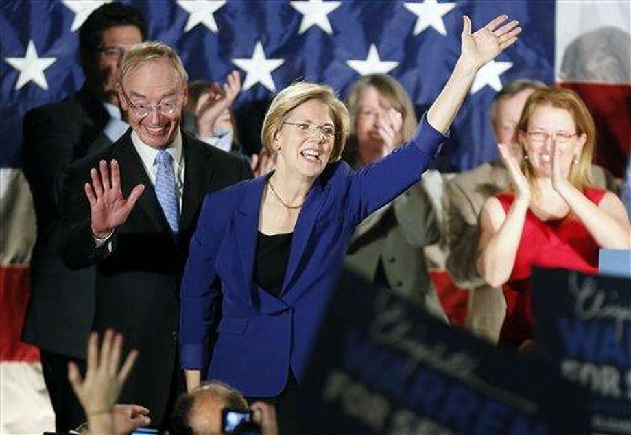 Democrat Elizabeth Warren, center, waves to the crowd with her husband Bruce Mann, left,  during an election night rally at the Fairmont Copley Plaza hotel in Boston after Warren defeated incumbent GOP Sen. Scott Brown in the Massachusetts Senate race. (AP Photo) Photo: AP / AP