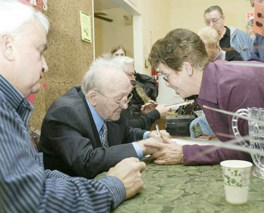 """Dispatch Staff Photo by JOHN HAEGERBoxing great Carmen Basilio ,center, signs """"The Onion Picker"""" by Gary Youmans for pat Gallagher of Chittenango during a book signing at the Canastota Public Library on Saturday, Feb. 2, 2008. Basilio use to give  Gallagher a ride to church on Sundays when she was a young girl."""
