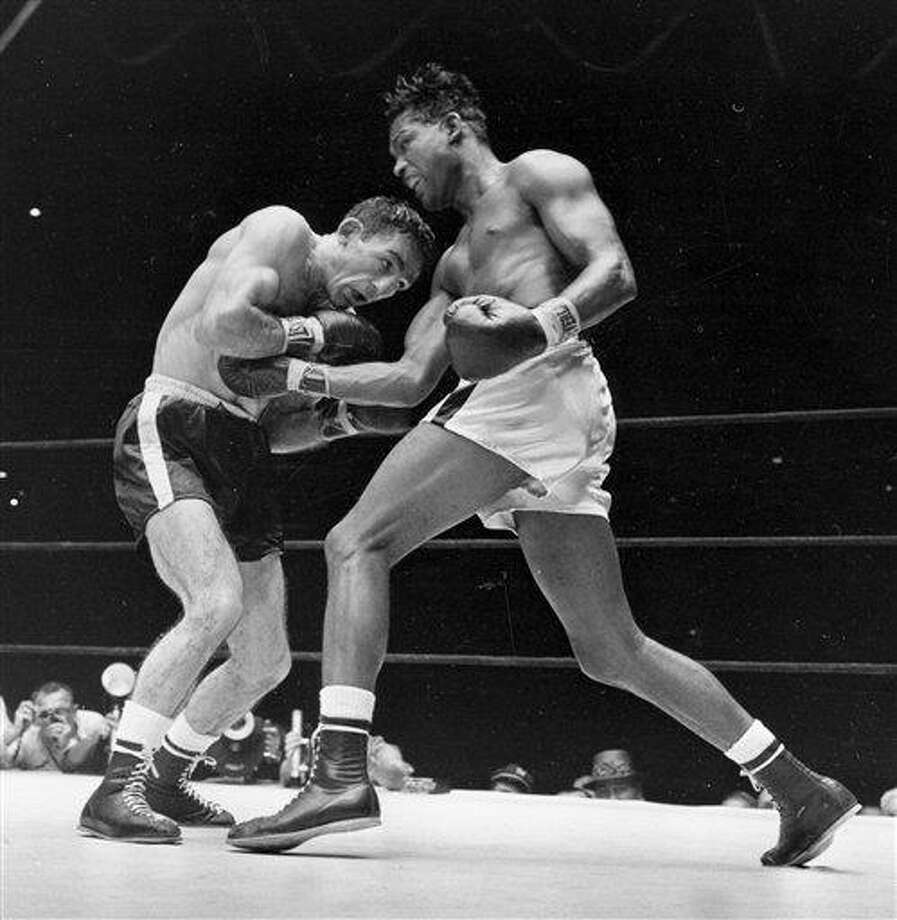 FILE - This Sept. 23, 2957 file photo shows world middleweight champion Sugar Ray Robinson, right, fighting challenger Carmen Basilio in the fifth round of a title fight at Yankee Stadium in New York. Basilio, a genial onion farmer's son with a malevolent left hook who wrested the world middleweight boxing crown from Sugar Ray Robinson in 1957, has died. He was 85. Edward Brophy, executive director of the Boxing Hall of Fame in upstate New York, says Basilio died early Wednesday morning, Nov. 7, 2012 in a Rochester, N.Y. hospital where he was being treated for pneumonia. (AP Photo/File) Photo: AP / AP
