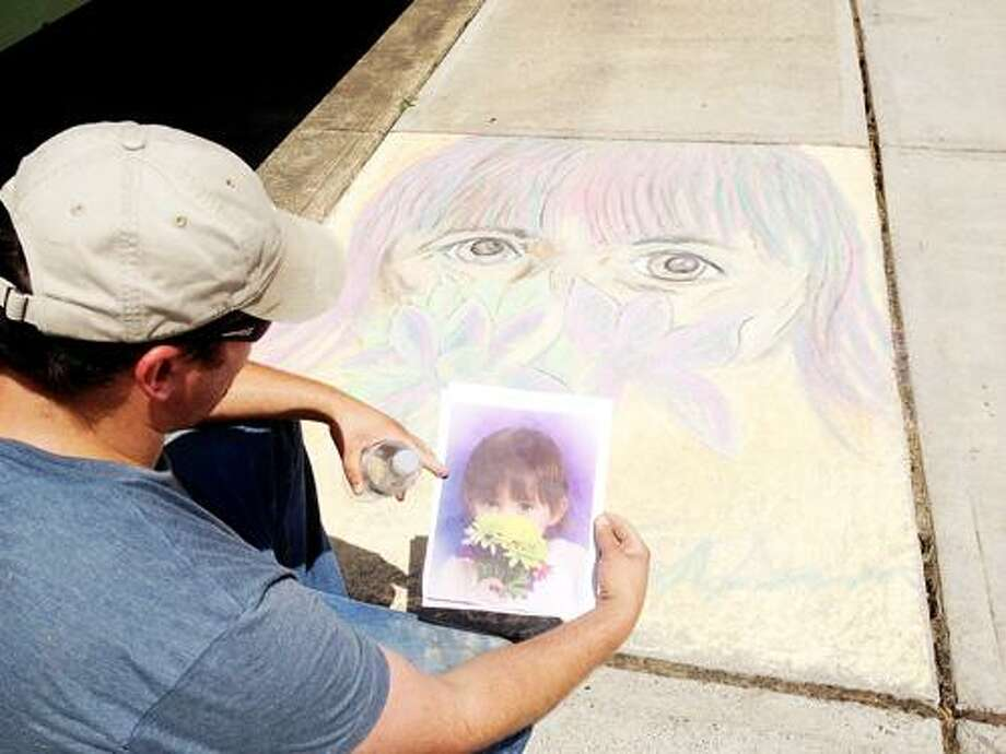 Photo by JOLENE CLEAVER Tom Gordon draws a picture of his daughter at Sylvan Beach's Chalk the Walk on Sunday, July 8, 2012.