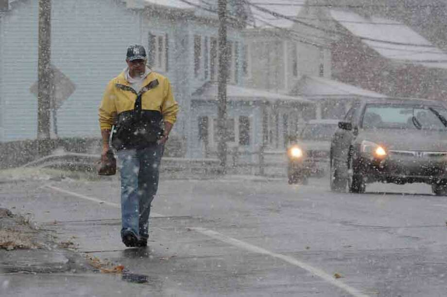 A lone pedestrian walks with traffic along Main Street in Branford as the snow began with the start of a coastal storm predicted to hit the area Wednesday. VM Williams/New Haven Register