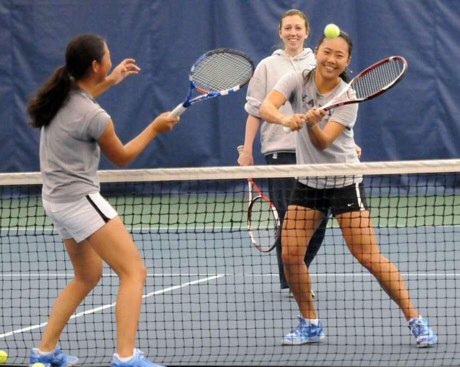 Yale women's tennis practicing at Cullman-Heyman Tennis center.  Hanna Yu left and Amber Li right in a drill overseen by coach Danielle McNamara. Mara Lavitt/New Haven Register5/3/12