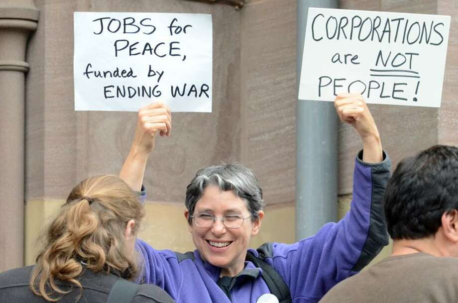 Debbie Elkin of New Haven holds a couple of protest signs Wednesday prior to going into the aldermanic meeting to attempt to persaude the aldermanic council to pass a resolution against corporate personhood. VM Williams/Register