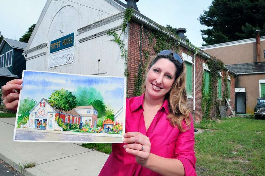 Keely Baisden Knudsen, artistic director of the Legacy Theatre, holds an artist's rendering of plans for the former Puppet House (background) in the Stony Creek section of Branford on 9/6/2012. Photo by Arnold Gold/New Haven Register   AG0461D