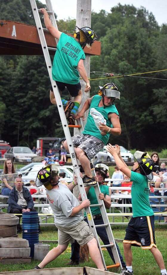 "Milford-- Members of the Bethany Hinman Station fire department use teamwork to ""save a baby"" during competition at the 41st Annual Engine 260 Antique Fire Apparatus Show and Muster. They are; Andrew Calhoun, top, Rich Benedict, center, Brendan Rieger, bottom right, Tom Sandora, left, and Jon Hubbard, bottom rear. Photo Peter Casolino/New Haven Register 09/08/2012"
