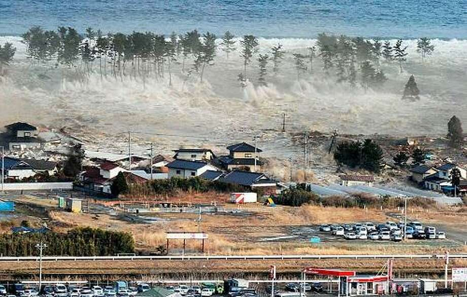 Waves of tsunami hit residences after a powerful earthquake in Natori, Miyagi prefecture (state), Japan, Friday, March 11, 2011.  The largest earthquake in Japan's recorded history slammed the eastern coast Friday. (AP Photo/Kyodo News) MANDATORY CREDIT, NO LICENSING ALLOWED IN CHINA, HONG KONG, JAPAN, SOUTH KOREA AND FRANCE Photo: ASSOCIATED PRESS / AP2011