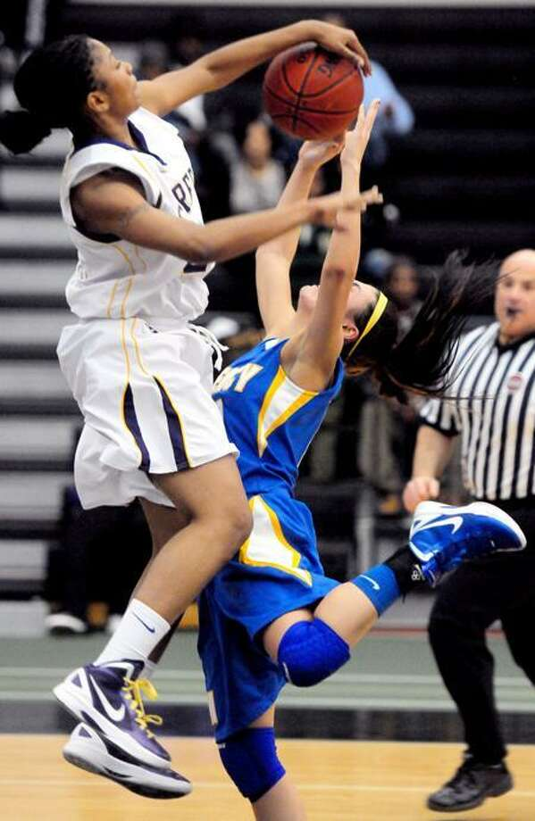 Tanaya Atkinson, left, of Career blocks the shot of Jordyn Nappi of Mercy late in the game at the Floyd Little Athletic Center in New Haven. Career beat Mercy. Photo by Arnold Gold/New Haven Register