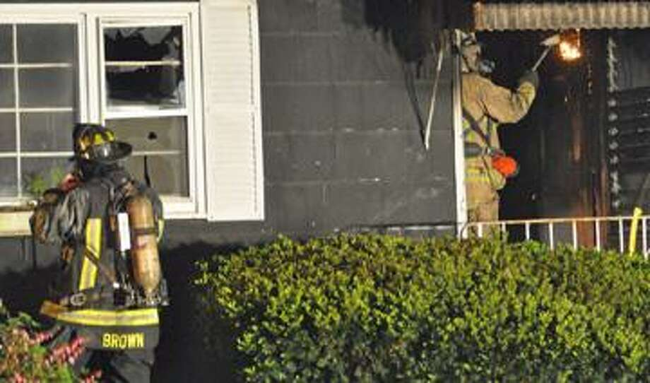 Torrington firefighters work Tuesday night's fire at 76 Barbero Dr. (RICK THOMASON / Register Citizen)