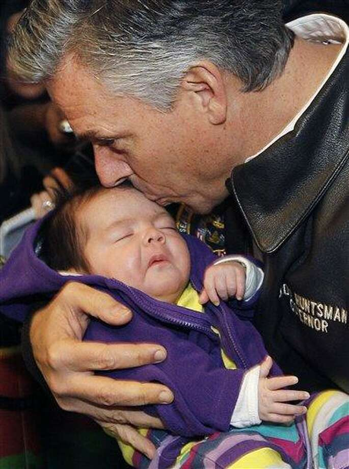 Republican presidential candidate and former Utah Gov. Jon Huntsman kisses 8-week-old Grace Lesperance while campaigning at Mary's Bakery and Cafe in Henniker, N.H., earlier this week. Associated Press Photo: AP / AP