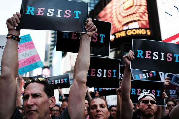 """NEW YORK, NY - JULY 26:  Dozens of protesters gather in Times Square near a military recruitment center to show their anger at President Donald Trump's decision to reinstate a ban on transgender individuals from serving in the military on July 26, 2017 in New York City. Trump citied the """"tremendous medical costs and disruption"""" for his decision.  (Photo by Spencer Platt/Getty Images)"""