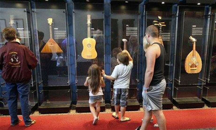 Visitors walk by the display of the instruments that is part of the touring National Guitar Museum exhibit on display at the Carnegie Science Center in Pittsburgh, through Sept. 30, 2012. The National Guitar Museum is a traveling guitar museum searching for a home. Museum director HP Newquist said the initial plan was to take it on the road for five years, to find out which city was the most hospitable. The museum is on a nine-city tour. (AP Photo/Keith Srakocic) Photo: AP / AP