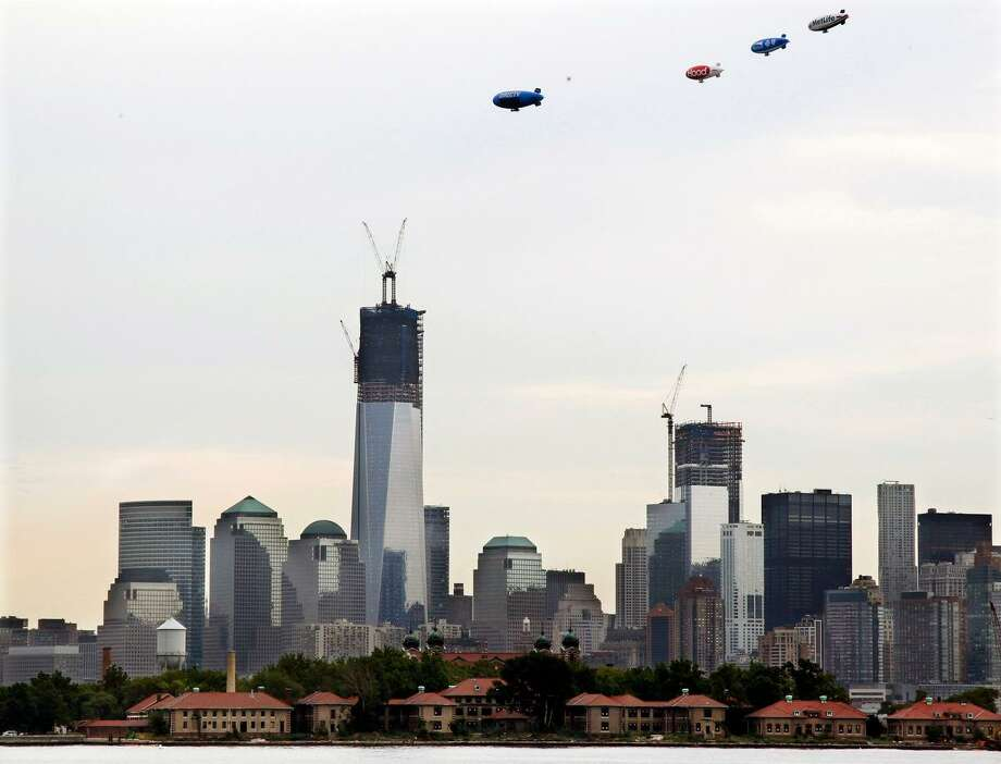Four advertising blimps, DirecTV, Hood, Horizon, and MetLife, fly together over the construction of One World Trade Center, now up to 104 floors, and the lower Manhattan skyline, Thursday, Sept. 6, 2012 in New York. Also under construction is 4 World Trade Center, right. Ellis Island is in the foreground. (AP Photo/Mel Evans) Photo: ASSOCIATED PRESS / AP2012