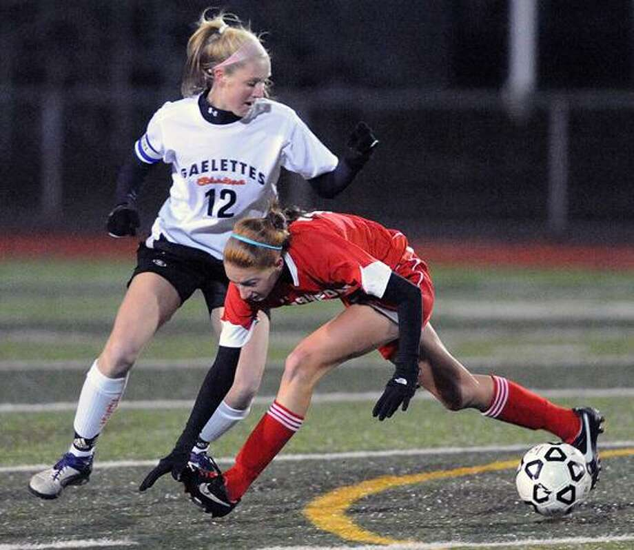 West Haven-- Branford's Tanya Altrui gets tripped up as Shelton's Megan Burke battle for possession during the first half.  Photo--Peter Casolino/New Haven Register. 11/06/12