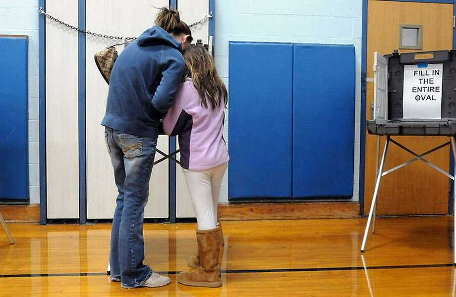 Super Storm Sandy didn't dampen turnout for voting at Momaugin Elementary School in East Haven; they were having an excellent turnout. Jennifer Bishop and her daughter Emilee, age 8, study Bishop's ballot. Mara Lavitt/New Haven Register