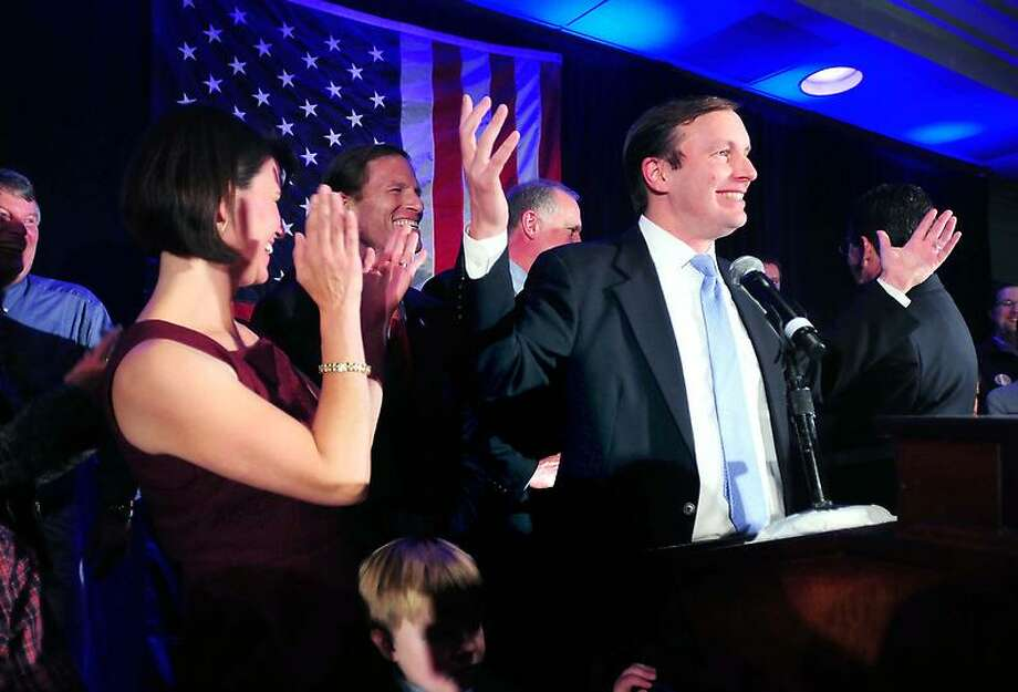 Cathy Murphy, left, applauds her husband, Chris Murphy, as he approaches the podium to declare victory over Linda McMahon at the Hilton Hotel in Hartford on Tuesday. Arnold Gold/New Haven Register