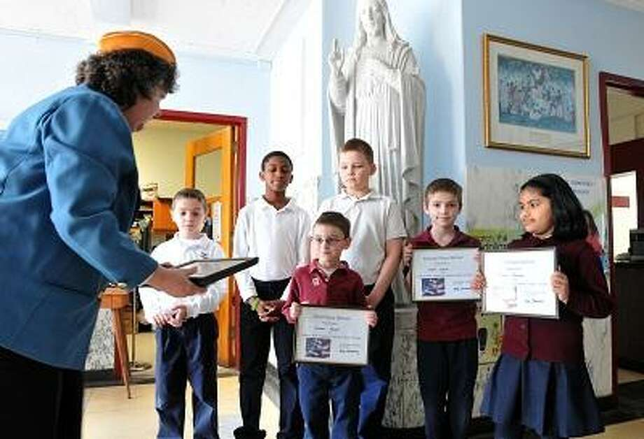 Derby--Evelyn Browning, President of the Catholic War Veterans 1562 auxiliary, hands out poster awards  to students at St. Mary-St. Michael school that won their patriotic poster competition. They are from left to right; Brandon Sibilia (2nd grade), Matthew Laurent (5th), Connor Hayes (Kindergarten), Igor Poliwoda (5th), Owen Clark (3rd) and Theresa Joseph (2nd). Hayes and Joseph both won national awards for the competition.  Photo- Peter Casolino/New Haven Register 03/09/12