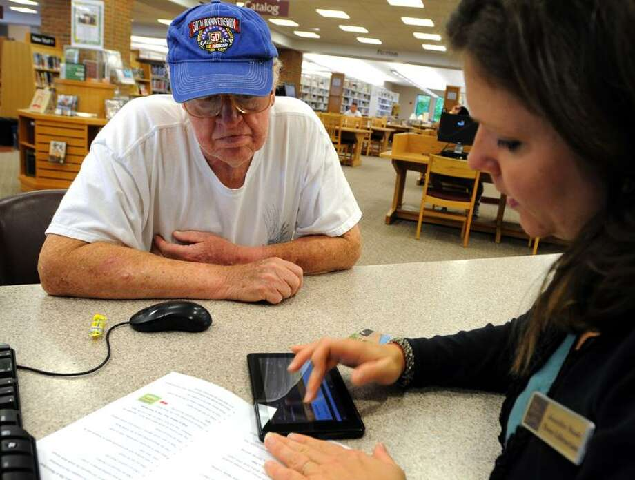 Don Magnan of Wallingford, 80, listens to librarian Jennifer Nash, 35, instruct him on  how to download e-books to his Kindle Fire e-reader at the Wallingford Public Library Friday, September 7, 2012 .Photo by Peter Hvizdak / New Haven Register Photo: New Haven Register / ©Peter Hvizdak /  New Haven Register