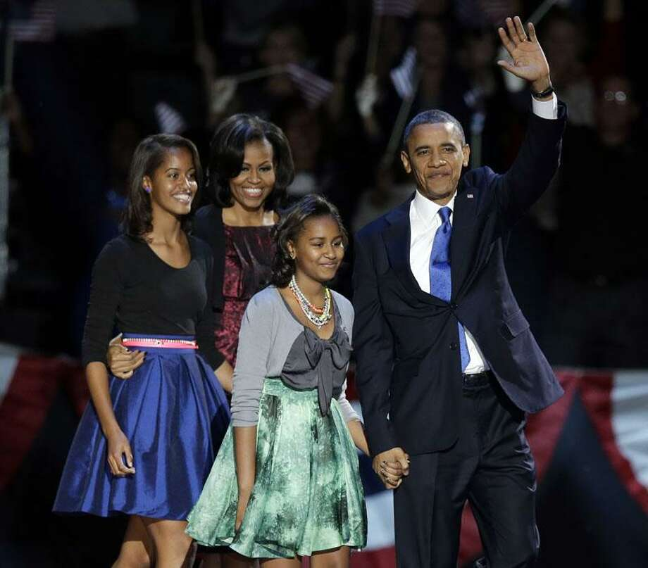 President Barack Obama waves as he walks on stage with first lady Michelle Obama and daughters Malia and Sasha at his election night party Wednesday, Nov. 7, 2012, in Chicago. President Obama defeated Republican challenger former Massachusetts Gov. Mitt Romney.(AP Photo/Chris Carlson) Photo: AP / AP