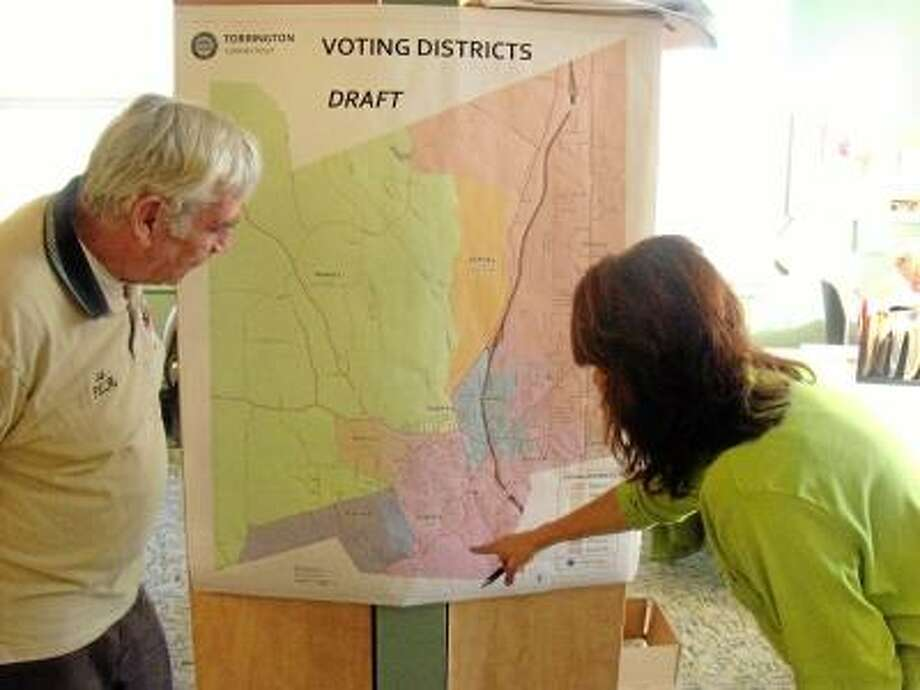 Ed Wilmont, incoming registrar of voters, observes as Nan Gallicchio, clerk at registrar of voters in Torrington, talks about the voting districts. Greg Seigle/For The Register Citizen
