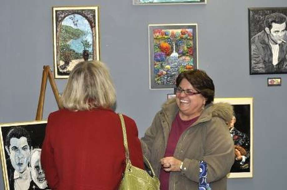RICK THOMASON / Register Citizen Lucy Guildford, right, shares a laugh with Debbie Kraft during Friday night's artist reception for Artist of the Month Joe Kopler in the Register Citizen's Newsroom Cafe. Guildford is a family friend from Harwinton, and Kraft, from Torrington, was Kopler's 8th grade history teacher. More than 70 people attended the event.