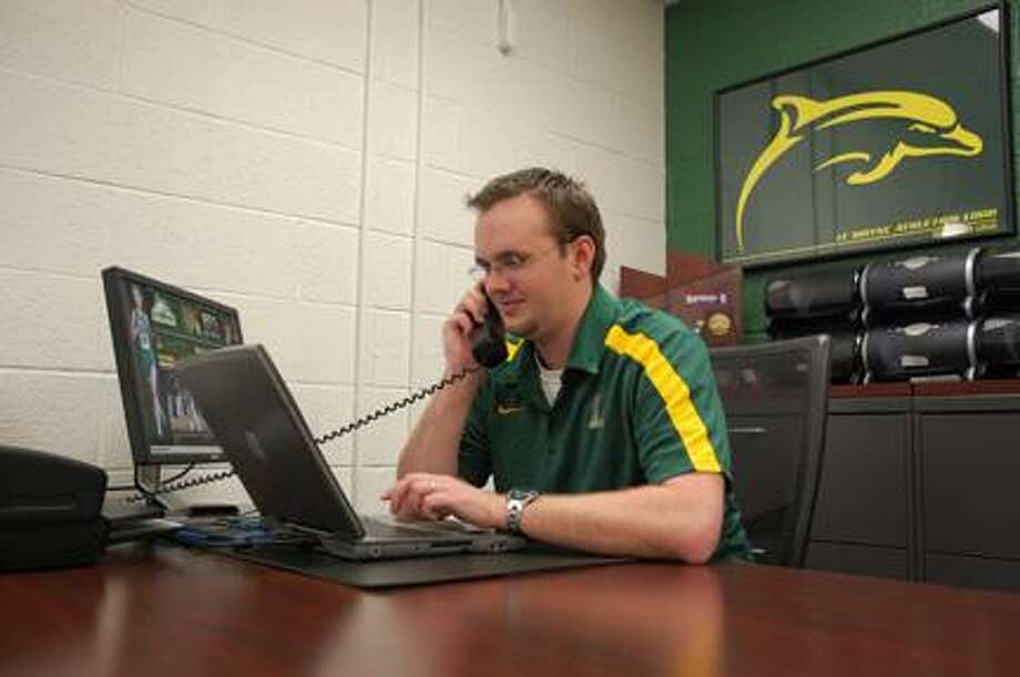 Submitted Photo Assistant sports information director Craig Lane works in his office at LeMoyne College in DeWitt.