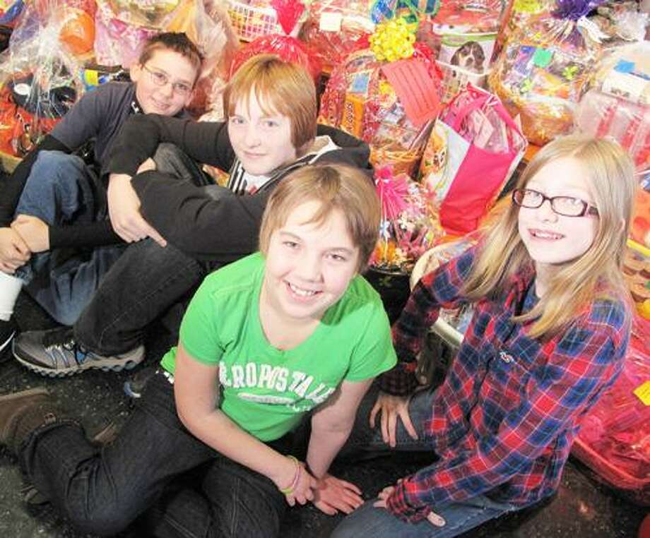 Dispatch Staff Photo by JOHN HAEGER (Twitter.com/OneidaPhoto) E. A. Wettle Elementary School sixth grader Lindsie Peters, 11, center in green, poses with classmates Jarrod Crane, 11, Cavan Woodcock, 12, and Paige Grunawald, 12, in front of baskets to be raffled off at the school to benefit Lindsie, who is battling lymphoproliferative cancer.