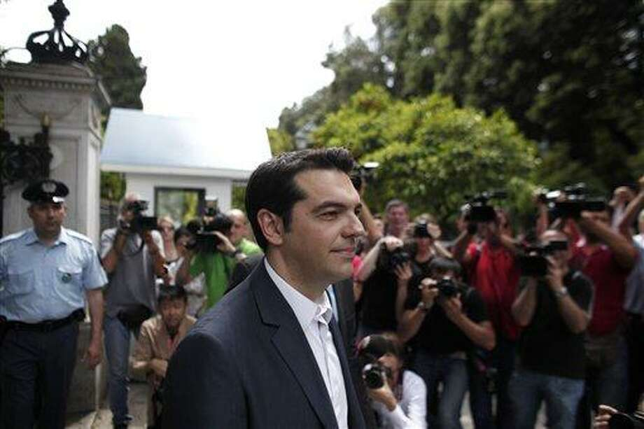 Alexis Tsipras, head of the Radical Left Coalition (SYRIZA), exits the Presidential Palace after his meeting with Greek President Karolos Papoulias, to formally take the mandate to form a coalition government in Athens Tuesday.  Associated Press Photo: AP / AP