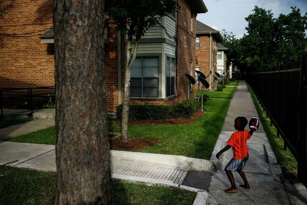 Jeremiah Cotton, 5, throws a football to his uncle, Shawn William at the Ewing Apartments Tuesday, July 25, 2017 in Houston. ( Michael Ciaglo / Houston Chronicle )