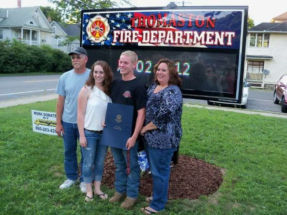 """SCOT ALLYN/Register Citizen The Terrier family stands proudly in front of a newly installed sign, set up in honor of their late son James """"Jimmy"""" Terrier Jr., a volunteer firefighter who died at 19. Jimmy's brother Jordan raised the money to buy the sign for Thomaston's volunteer department. Jordan is a member, and so was Jimmy."""