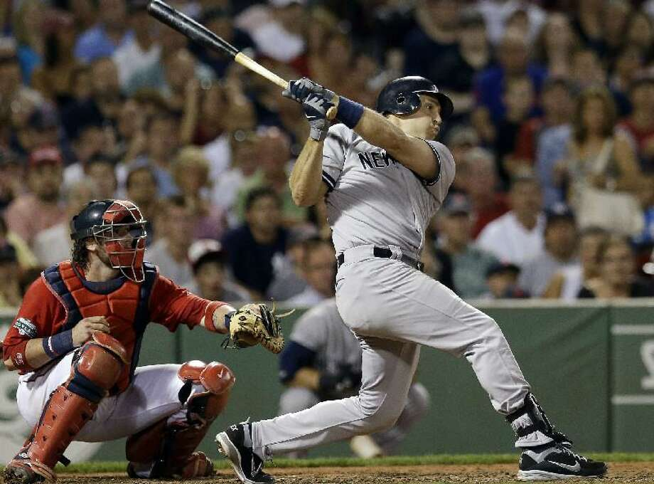ASSOCIATED PRESS New York Yankees first baseman Mark Teixeira follows through on a two-run triple as Boston Red Sox catcher Jarrod Saltalamacchia watches in the seventh inning of Friday's game at Fenway Park in Boston. The Yankees won 10-8.