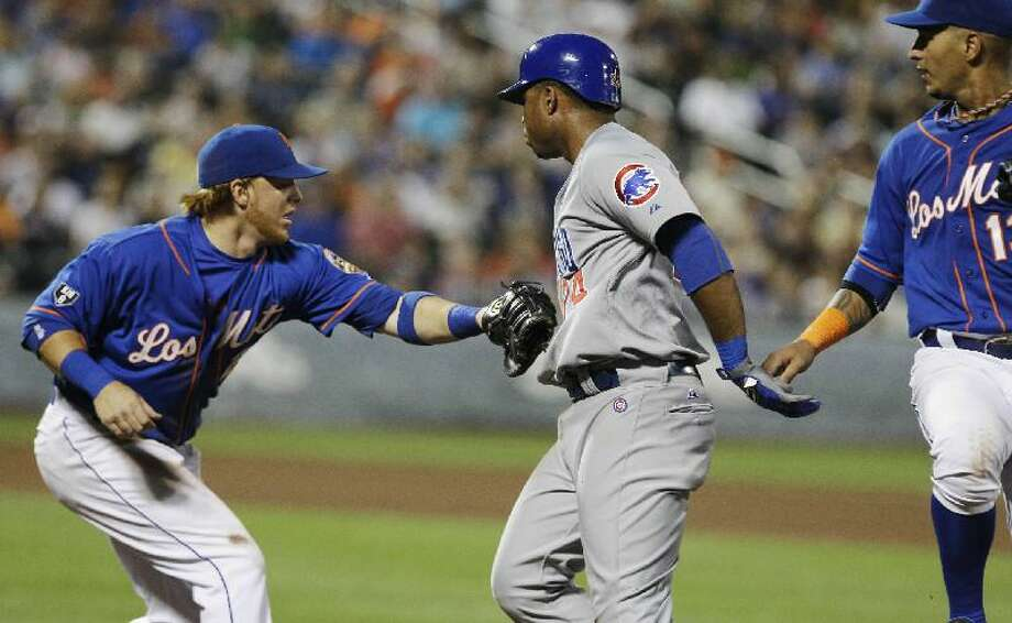 ASSOCIATED PRESS New York Mets second baseman Justin Turner, left, tags out Chicago Cubs' Luis Valbuena, center, as Mets' Ronny Cedeno watches during the fifth inning of Friday's game at Citi Field in New York. The Mets lost 8-7.
