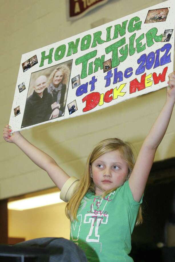 """Dispatch Staff Photo by JOHN HAEGER <a href=""""http://twitter.com/oneidaphtoto"""">twitter.com/oneidaphtoto</a>    Emma Tyler , 7, holds up a sign honoring her father Tim Tyler before the start of the  finals of the  Canastota Dick New Tournament  on Saturday Jan. 7, 2012 in Canastota."""