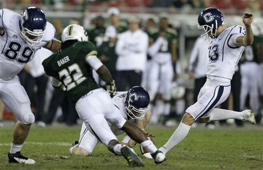 Connecticut kicker Chad Christen (13) boots a third-quarter field goal as Cole Wagner (86) holds during an NCAA college football game against South Florida, Saturday, Nov. 3, 2012, in Tampa, Fla. Connecticut's John Delahunt (89) blocks South Florida's George Baker (22). (AP Photo/Chris O'Meara) Photo: AP / AP