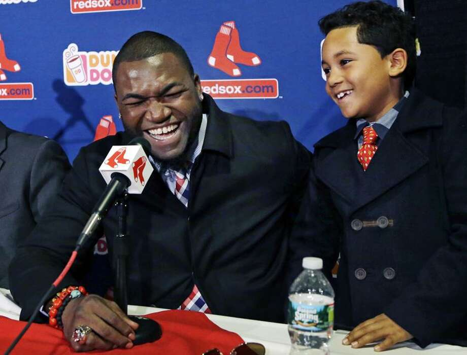 Boston Red Sox's David Ortiz laughs with his son D'Angelo, 8, during a baseball news conference, Monday, Nov. 5, 2012, at Fenway Park in Boston. Ortiz announced that he has finalized a $26 million, two-year contract, which includes bonuses that could raise the value to $30 million. (AP Photo/Elise Amendola) Photo: AP / AP2012