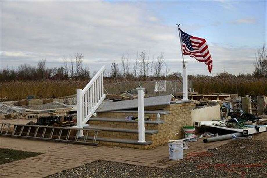 An American flag flies from the front steps of a home that was washed away by Superstorm Sandy in Staten Island, New York, Monday, Nov. 5, 2012.  (AP Photo/Seth Wenig) Photo: AP / AP