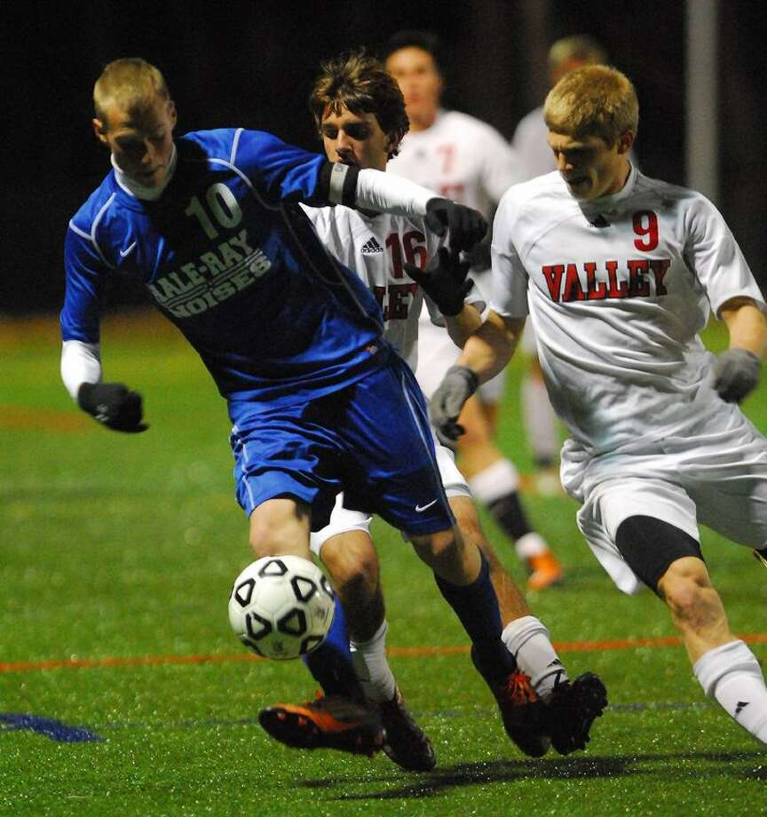 Catherine Avalone/The Middletown PressHale Ray's Erick Tung and Valley Regional senior Jonathan Luster battle for possession in the first half of the Shoreline Championship match at Indian River Athletic Complex in Clinton Monday night.